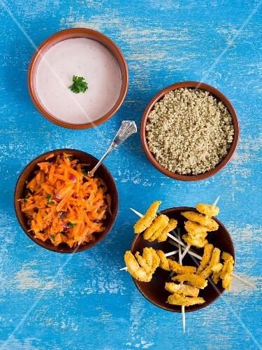 Chicken tandoori skewers with quinoa, carrot salad and raita in small bowls