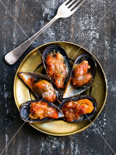 Spicy gratinated mussels on a gold-coloured plate