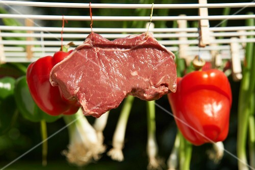 A raw pork steak and vegetables hanging on a washing line