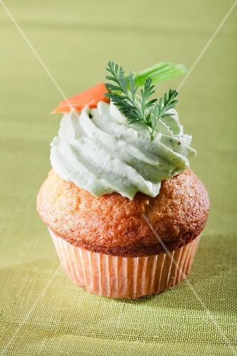 A carrot cupcake decorated with green cream