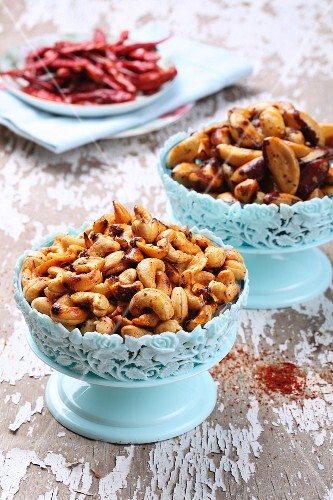 Spicy roasted cashew nuts and Brazil nuts in light blue bowls