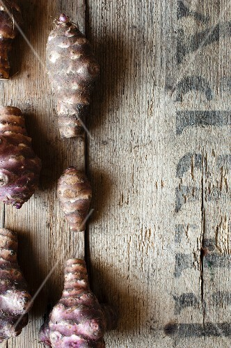 A row of Jerusalem artichokes on a rustic wooden surface
