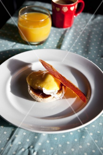 Eggs Benedict with a slice of crispy Parma ham on a breakfast table