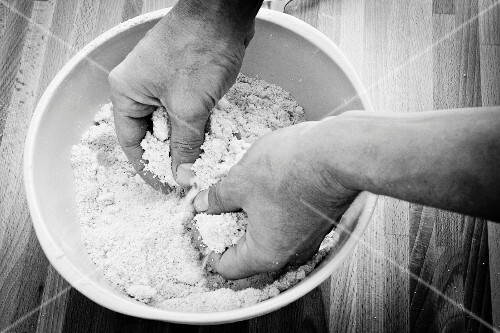 Ingedients for shortcrust being mixed by hand (black-and-white image)