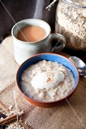 Porridge with yogurt and cinnamon served with a mug of tea