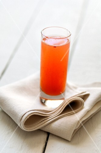 A glass of fruit juice on a fabric napkin