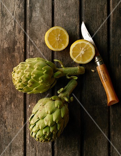 Two artichokes, a halved lemon and a knife on a wooden surface