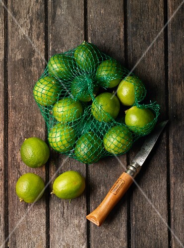 Limes in a net with a knife on a wooden surface