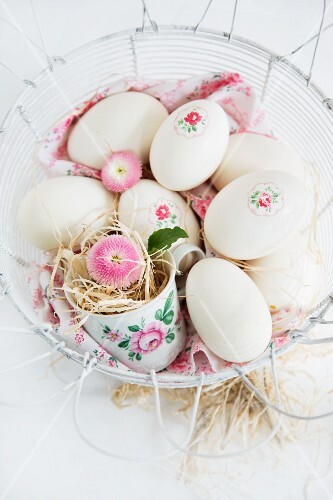 Easter eggs decorated with napkin decoupage in nest of straw in wire basket