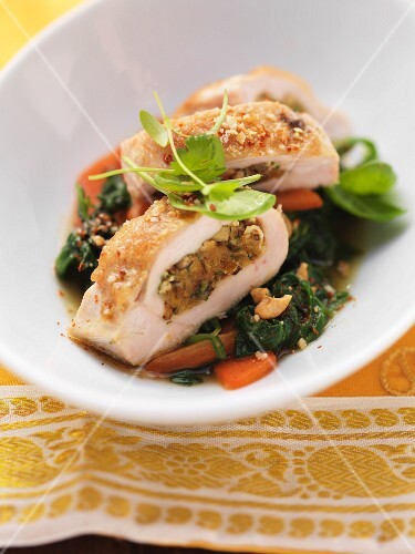 Stuffed chicken breast on a bed of spinach with cashew nuts