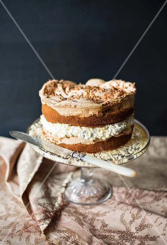 A layered sponge cake with nuts and meringue on a cake stand