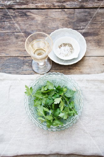 Parsley in a glass bowl with a glass of wine and a salt and pepper mixture behind it