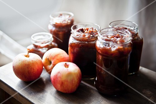 Jars of homemade apple chutney and fresh apples