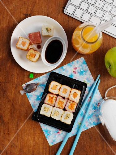 Sushi, orange juice and an apple in an office