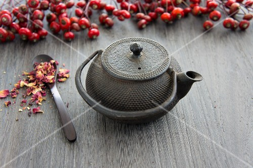 A teapot, rosehips and dried wild rose petals
