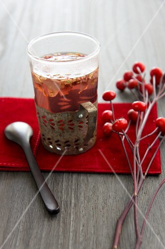 A glass of rosehip tea and fresh rosehips