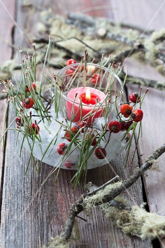 Ice candle lantern decorated with rosehips