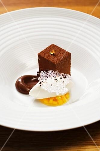 A chocolate cream cube and ice cream on mango jelly