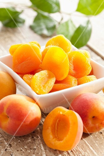 Fresh and dried apricots on a wooden table