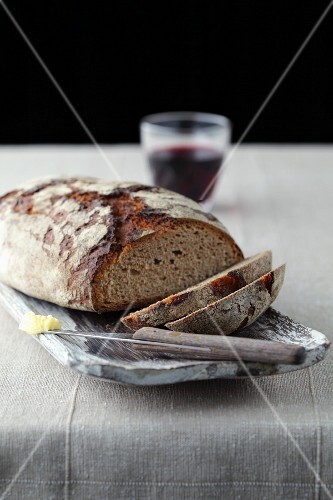 Sliced bread with red wine and a knife with butter