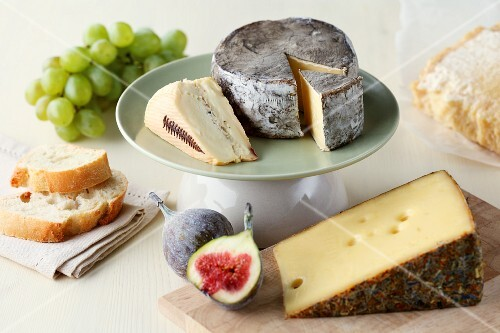 Various types of cheese on a wooden board and on a cake stand with figs, grapes and a cheese knife
