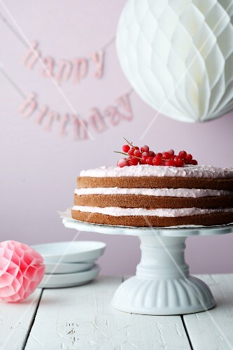 A redcurrant cake on a cake stand with the word 'Happy Birthday in the background