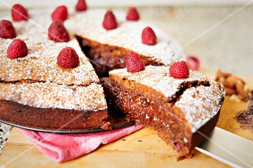A brownie chocolate tart with raspberries, sliced