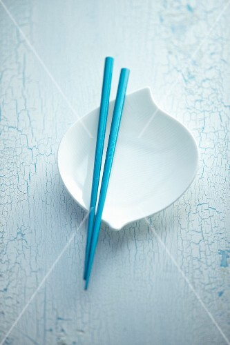 Blue chopsticks balanced over a white bowl