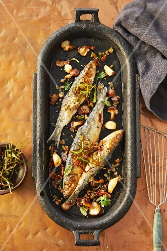 Roast sardines with vegetables and herbs in an iron pan (seen from above)
