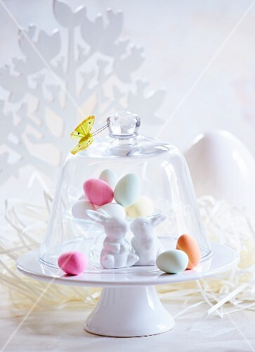 Colourful Easter eggs and Easter bunnies under a glass cloche