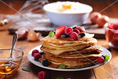 Pancakes with fresh summer berries and mint leaves