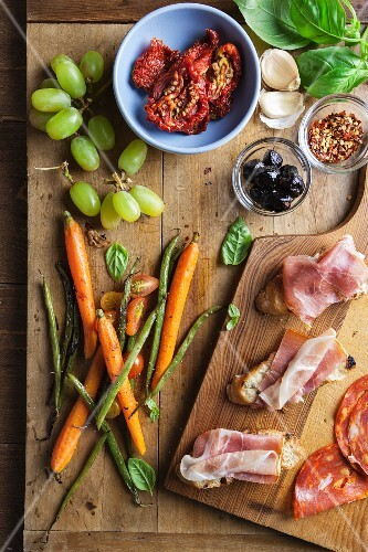 Ingredients for appetizers on a chopping board: Prosciutto, carrots, asparagus, dried tomatoes, olives, grapes basil