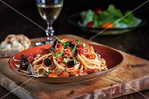 Spaghetti puttanesca (olives, capers, tomatoes and parsley) with white wine, bread and salad