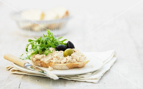 A slice of bread topped with chicken pate, olives and rocket