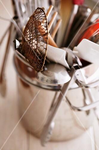 Various kitchen utensils in a metal pot