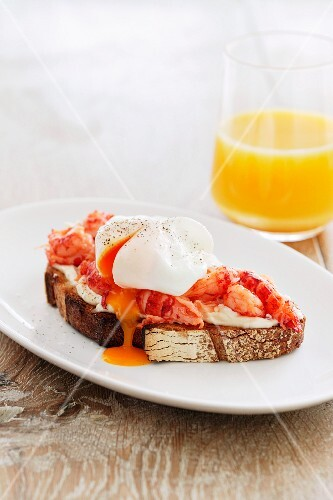 A slice of bread topped with prawns and a poached egg