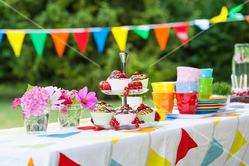 A table laid in a garden for a birthday party