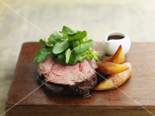 Beefsteak and chips on wooden board