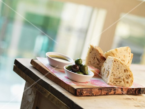 Olives, bread and oil on a wooden board