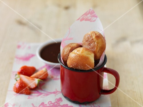 Mini doughnuts in a cup, fresh strawberries and chocolate sauce