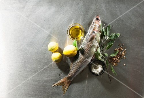 An arrangement of fish, lemons, olive oil, sage and spices