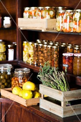 Various jars of preserves, fresh lemons and green asparagus
