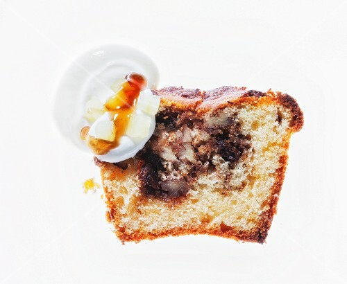 A slice of vanilla cake with nuts, raisins, cinnamon, cream and maple syrup