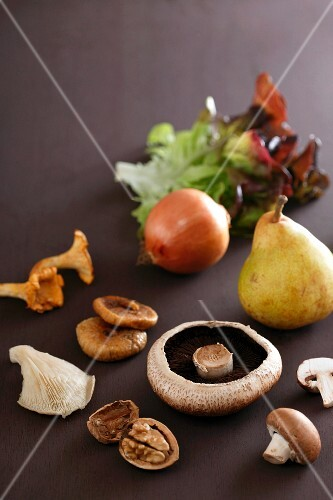 An arrangement of mushrooms, dried figs, walnuts, a pear, an onions and lettuce