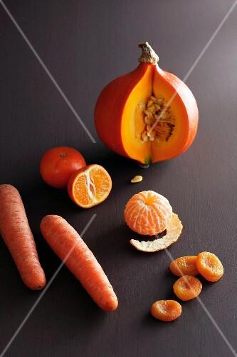 An orange pumpkin, mandarins, carrots and dried apricots