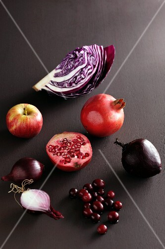 A red cabbage, a pomegranate, a beetroot, cranberries, an onion and an apple