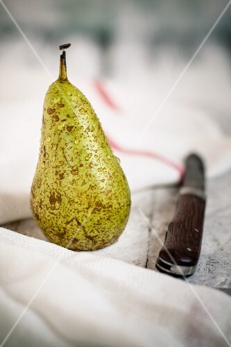 A freshly washed pear on a white wooden board
