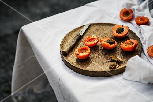Halved apricots on a wooden plate