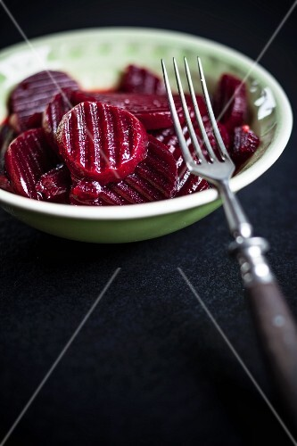 Pickled beetroot in a bowl with a fork