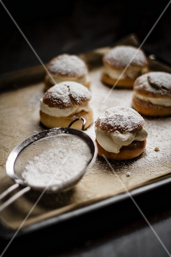 Semlor (Swedish cakes) on a baking tray next to a sieve of icing sugar